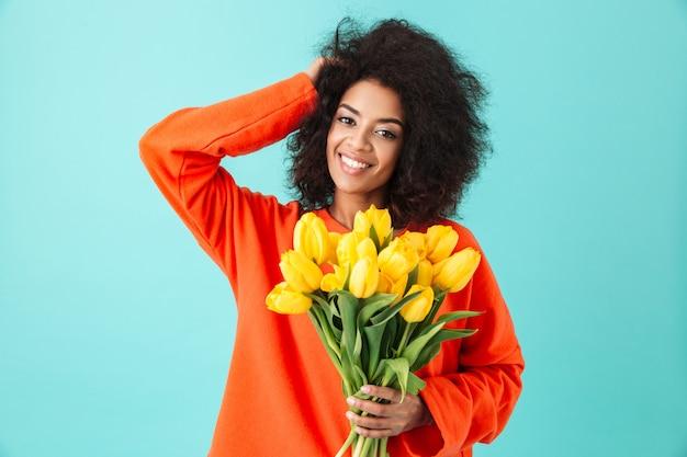 Zadowolona amerykanka z kudłatymi włosami i trzymająca bukiet wiosennych żółtych kwiatów, odizolowanych na niebieskiej ścianie