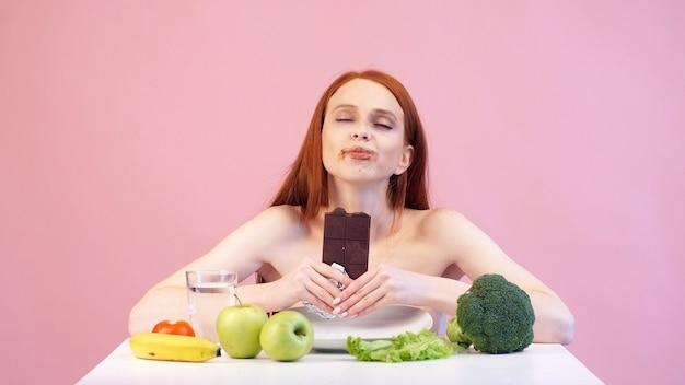 Zadowolona anoreksyjna dziewczyna łapczywie je czekoladę. zaburzenia odżywiania. anoreksja