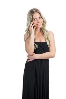Zadowolona atrakcyjna blondynka z czarny koktajl pozowanie