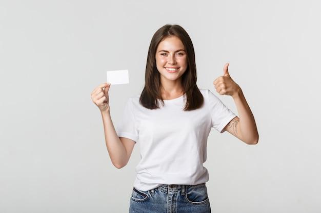 Zadowolona atrakcyjna dziewczyna pokazuje kartę kredytową i kciuki do góry.