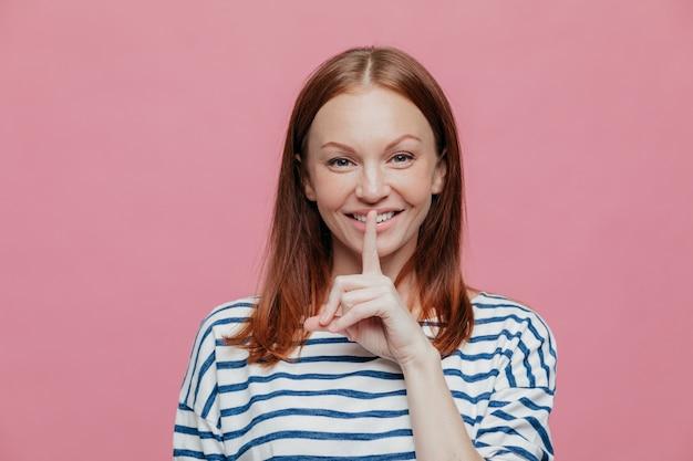 Zadowolona atrakcyjna kobieta o brązowych włosach, łagodnym uśmiechu, trzyma palec wskazujący na ustach, pokazuje gest ciszy
