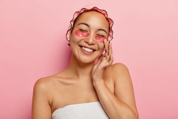 Zadowolona azjatka nakłada plastry kolagenowe zmniejszające obrzęki, pozytywnie się uśmiecha, pokazuje białe zęby, nosi miękki czepek, stoi owinięta ręcznikiem, ma zabiegi kosmetyczne przed randką z chłopakiem