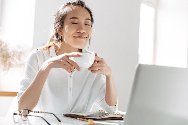 Zadowolona azjatycka biznesowa kobieta pije kawę i cieszy się z zamkniętymi oczami, siedząc przy stole w biurze