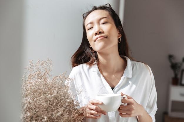 Zadowolona azjatycka biznesowa kobieta pije kawę i relaksuje się z zamkniętymi oczami, stojąc w pobliżu okna w biurze