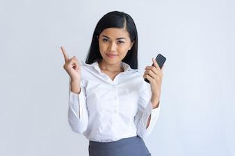 Zadowolona Azjatycka dziewczyna z telefonem ma pomysł