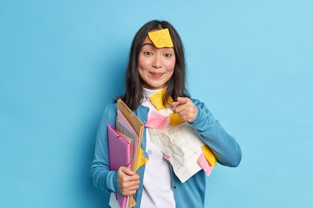 Zadowolona azjatycka pracownica biurowa z zadowolonym wyrazem twarzy trzyma folder i wskazuje bezpośrednio w aparacie