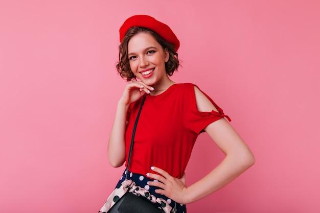 Zadowolona biała kobieta w eleganckim francuskim stroju pozuje z radosnym uśmiechem. portret dziewczyny debonair w czerwonych ubraniach.