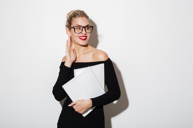 Zadowolona biznesowa kobieta w sukni i okularach trzyma dokumenty
