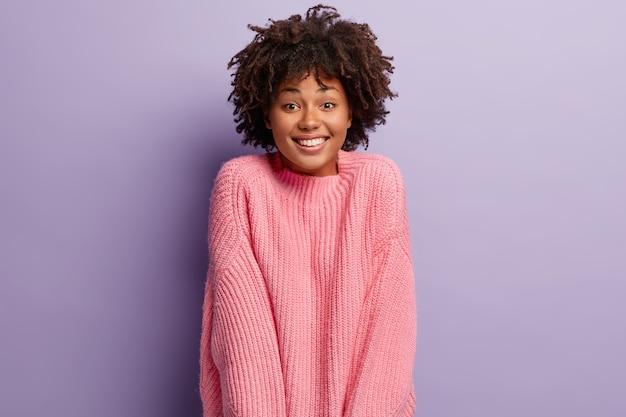 Zadowolona, błoga kobieta wygląda z radosnym, przyjaznym wyrazem twarzy, zadowolona z otrzymania propozycji, nosi dzianinowy zimowy luźny sweter, ma zdrową skórę, bez makijażu, jest zadowolona, odizolowana na fioletowej ścianie