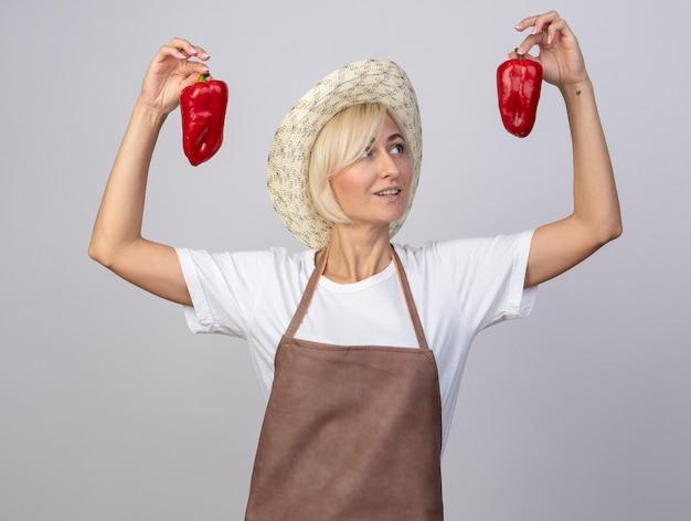 Zadowolona blond ogrodniczka w średnim wieku w mundurze w kapeluszu podnosząca papryki patrząca na jedną z nich