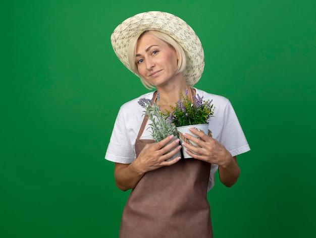 Zadowolona blond ogrodniczka w średnim wieku w mundurze w kapeluszu trzymająca doniczki izolowane na zielonej ścianie z miejscem na kopię