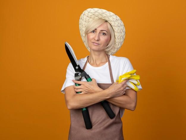 Zadowolona blond ogrodniczka w średnim wieku w mundurze w kapeluszu, trzymająca skrzyżowane ręce, trzymająca nożyce do żywopłotu i rękawiczki ogrodnicze
