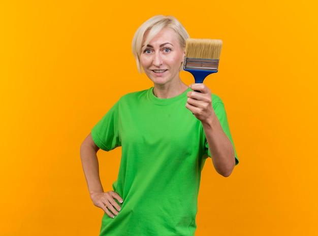 Zadowolona blond słowianka w średnim wieku, patrząc z przodu, pokazując pędzel, trzymając rękę na talii odizolowaną na żółtej ścianie z miejscem na kopię