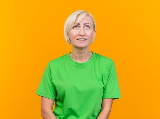 Zadowolona blond słowiańska kobieta w średnim wieku patrząc na białym tle na żółtym tle z miejsca na kopię