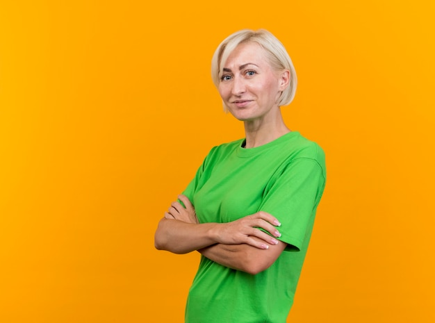 Zadowolona Blond Słowiańska Kobieta W średnim Wieku Stojąca Z Zamkniętą Postawą W Widoku Profilu, Patrząc Na Kamerę Odizolowaną Na żółtym Tle Z Przestrzenią Do Kopiowania Darmowe Zdjęcia