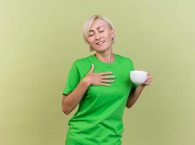 Zadowolona blond słowiańska kobieta w średnim wieku trzymająca filiżankę herbaty kładąca dłoń na klatce piersiowej z zamkniętymi oczami odizolowana na oliwkowej ścianie z miejscem na kopię