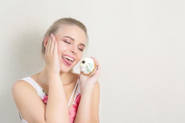 Zadowolona blondynka bawi się słodkim deserem z kremem maślanym. miejsce na tekst