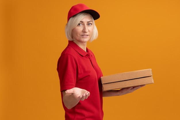 Zadowolona blondynka doręczycielka w czerwonym mundurze i czapce stojąca w widoku z profilu trzymająca paczki z pizzą patrząca na przód wyciągając rękę do przodu