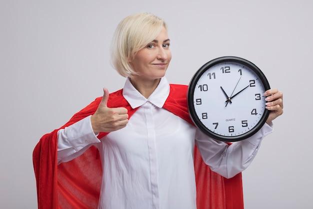 Zadowolona blondynka superbohaterka w średnim wieku w czerwonej pelerynie trzymająca zegar patrząc na przód pokazujący kciuk na białym tle na białej ścianie