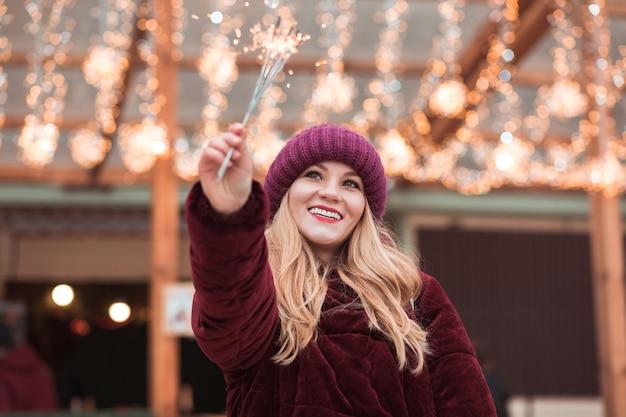 Zadowolona blondynka ubrana w stylowe ubrania, trzymająca świecące ognie na jarmarku bożonarodzeniowym w kijowie