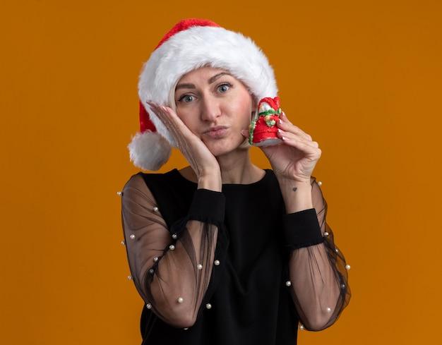 Zadowolona blondynka w średnim wieku w świątecznej czapce trzymająca mały posąg bałwana patrząc na kamerę, trzymając rękę na twarzy odizolowaną na pomarańczowym tle z miejscem na kopię