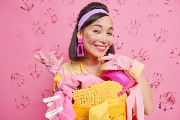 Zadowolona brunetka azjatka pochyla się przy koszu na bieliznę, uśmiechając się szczęśliwie będąc brudna po sprzątaniu, nosi gumowe rękawice ochronne, pałąk na białym tle nad różową ścianą