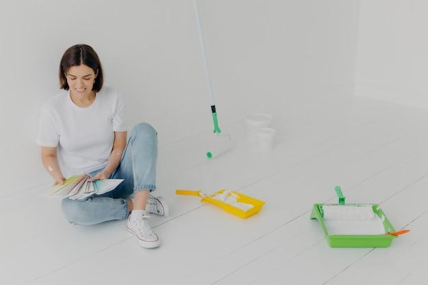 Zadowolona brunetka kobieta wybiera kolor z próbek