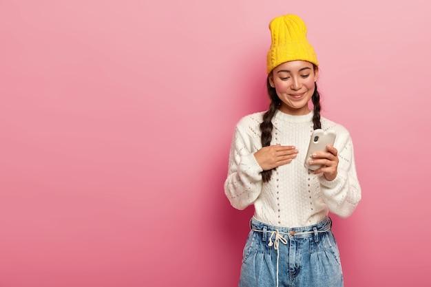 Zadowolona brunetka koreanka za pomocą telefonu komórkowego na różowym tle