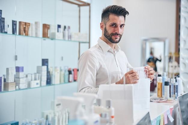 Zadowolona brunetka mężczyzna stojąca w pół pozycji w recepcji podczas rozmowy o swoich zakupach