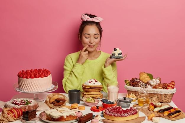 Zadowolona brunetka trzyma małą kremową babeczkę, piecze wiele deserów na święta nowego roku lub święta, demonstruje swoje kulinarne zdolności