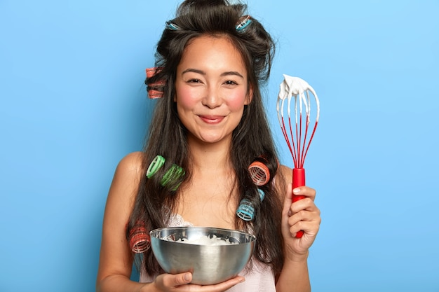 Zadowolona brunetka ubija śmietanę do miski, nosi lokówki