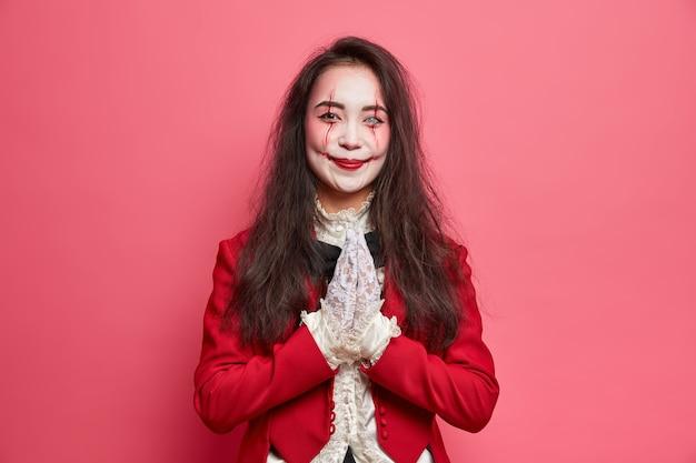 Zadowolona brunetka z krwawym makijażem trzyma dłonie przyciśnięte do siebie, prosi o przysługę, nosi czerwony kostium i koronkowe rękawiczki pozuje na różowej ścianie