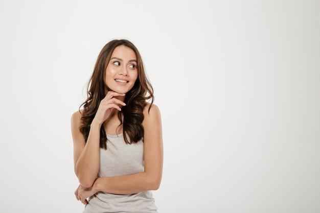 Zadowolona brunetki kobieta pozuje z ręki pobliską twarzą i patrzeje daleko od nad popielatym