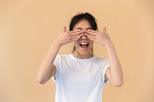 Zadowolona chińska kobieta ubrana w prosty t-shirt zakrywający oczy rękami odizolowanymi na beżowej ścianie w studio