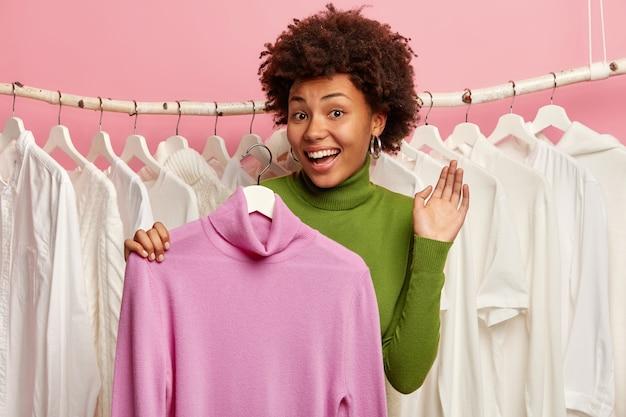 Zadowolona ciemnoskóra kobieta wybiera strój, trzyma fioletowy sweter na wieszaku, stoi przy szafie z ubraniami