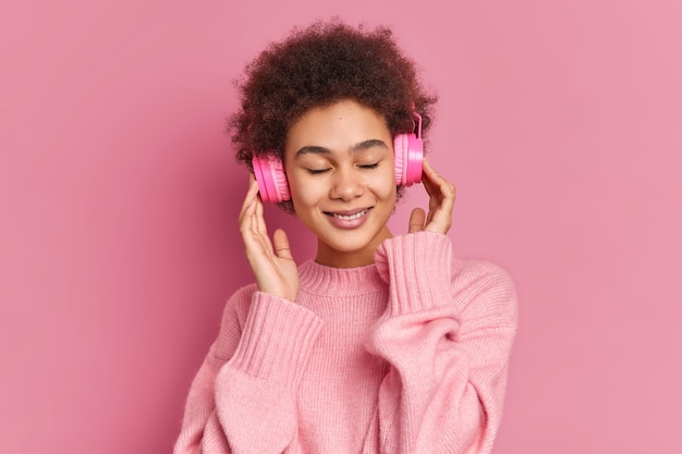 Zadowolona ciemnoskóra młoda kobieta lubi słuchać przyjemnej melodii, trzyma ręce na słuchawkach stereo, zamyka oczy, nosi swobodny sweter