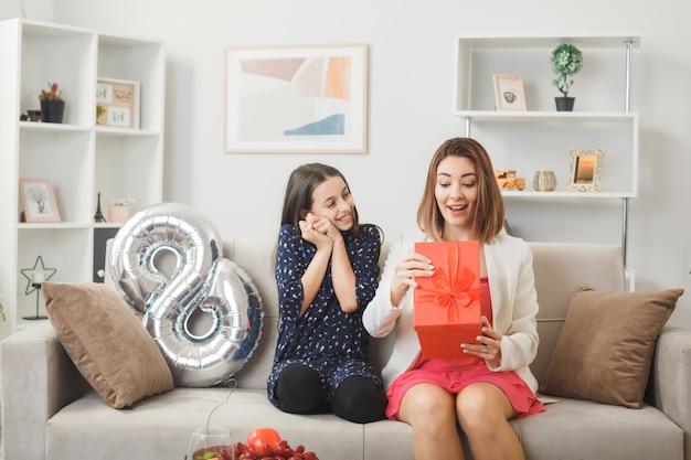 Zadowolona córka daje prezent zaskoczonej mamie w szczęśliwy dzień kobiety siedzącej na kanapie w salonie