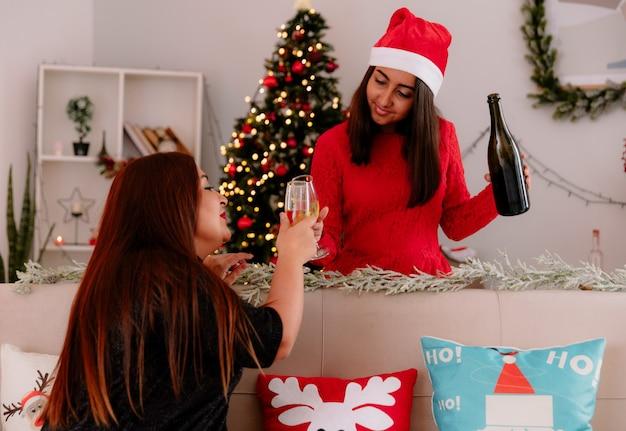 Zadowolona córka i matka siedzą na kanapie brzęk kieliszkami szampana, ciesząc się świątecznymi chwilami w domu