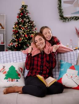 Zadowolona córka przykrywa kocem swoją matkę czytającą książkę siedzącą na kanapie i przytula się, ciesząc się świątecznymi chwilami w domu