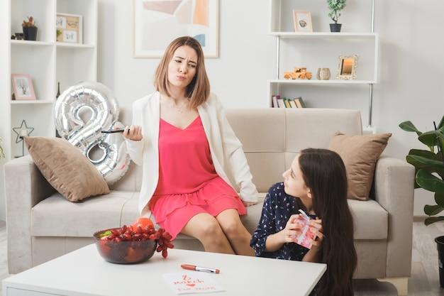Zadowolona córka trzyma prezent patrząc na niezadowoloną matkę siedzącą na kanapie w szczęśliwy dzień kobiet w salonie