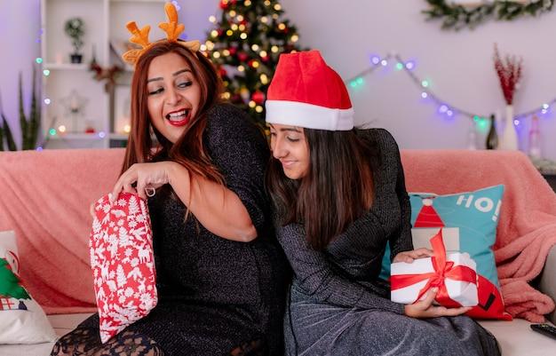 Zadowolona córka w czapce mikołaja trzyma pudełko i patrzy na prezent matki siedząc na kanapie tyłem do siebie, ciesząc się świątecznymi w domu