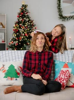 Zadowolona córka wkłada czapkę mikołaja na głowę matki siedzącej na kanapie i cieszącej się świątecznymi chwilami w domu