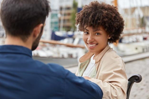 Zadowolona czarna nastolatka ubrana w kurtkę, siedzi na ławce razem z przystojnym facetem