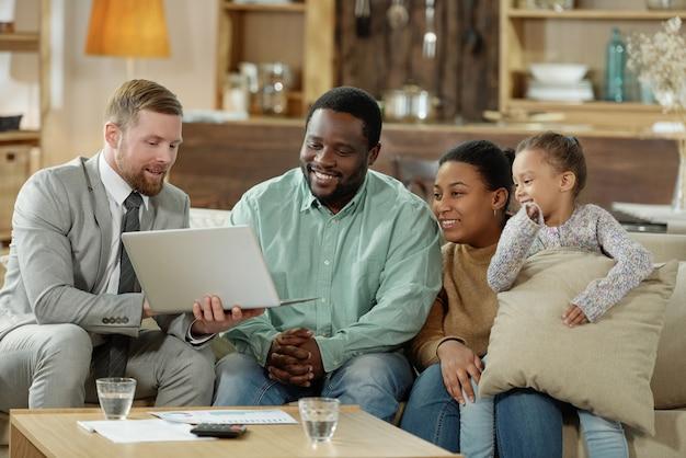 Zadowolona czarna rodzina z małą dziewczynką siedzącą na kanapie z eleganckim mężczyzną konsultującym ich w sprawie kredytu hipotecznego
