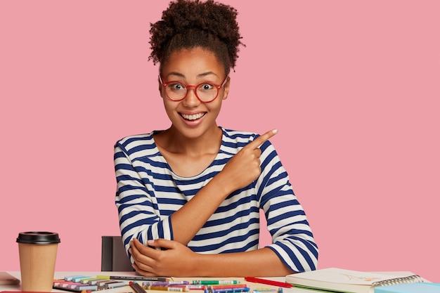 Zadowolona czarna rzemieślniczka w pasiastych ubraniach, pokazuje wolne miejsce na różowej ścianie, pracuje nad nowym szkicem w zeszycie z kredkami, pije, pije kawę, pracuje w domu, ma kreatywne umiejętności