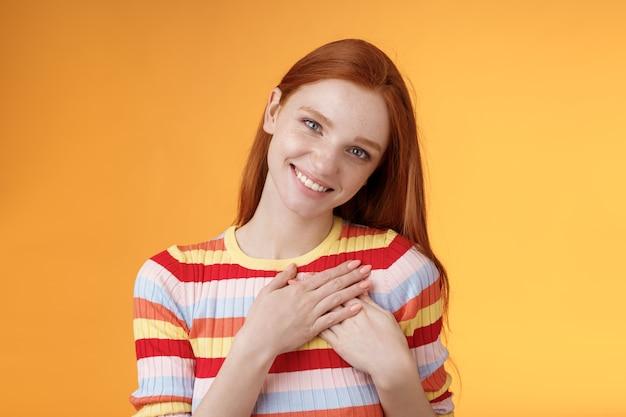 Zadowolona delikatna kobieca, ładna ruda kobieta otrzymuje komplement spowiedź dotknąć serduszko ciepło najdroższa chwila uśmiecham się zachwycona ślicznotka zachowuje miłość w duszy, stojąc na pomarańczowym tle.