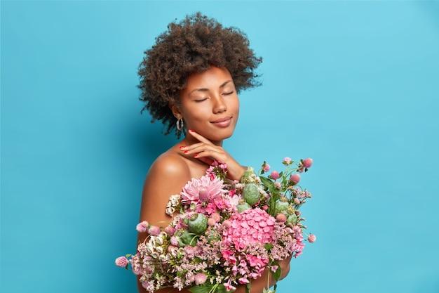 Zadowolona, delikatna modelka dotyka szczęki, zamyka oczy, cieszy się pięknym momentem pozuje półnaga z bukietem pięknych kwiatów odizolowanych na niebieskiej ścianie