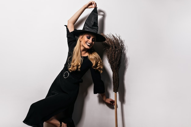 Zadowolona długowłosa wiedźma tańczy z miotłą. sympatyczna czarodziejka bawiąca się w halloween.