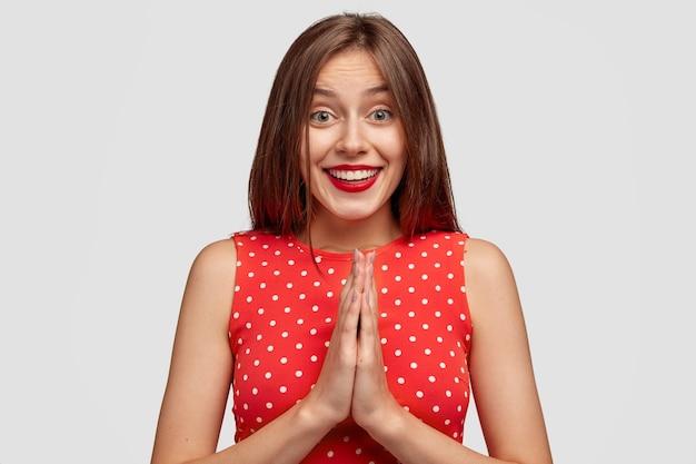 Zadowolona, dobrze wyglądająca brunetka młoda kobieta trzyma dłonie razem
