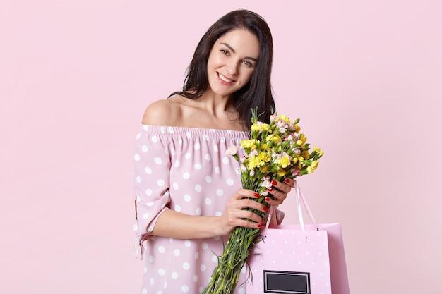 Zadowolona, dobrze wyglądająca kobieta o ciemnych włosach, szerokim uśmiechem, trzyma kwiaty i torebkę prezentową, nosi letnią sukienkę z radosnym wyrazem, modele na jasnoróżowym